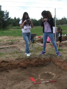 Μαθήτριες φωτογραφίζουν τα ακίνητα ευρήματα του ανασκαφικού τετραγώνου. Χρήση κλίμακας και βέλους (τοποθέτηση πάντα προς βορρά) για τον σωστό προσανατολισμό.