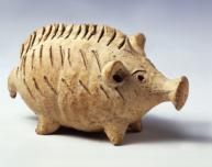 Πήλινο ειδώλιο σε μορφή χοίρου, που προφανώς χρησίμευε και ως κουδουνίστρα, αφού στο κοίλο εσωτερικό του υπάρχουν μικρές πέτρες ή σπόροι. Πρόκειται για συνήθη τύπο παιδικού παιχνιδιού που πιθανότατα παρήχθη σε εργαστήριο της Σαλαμίνας της Κύπρου, 600-480 π.Χ.