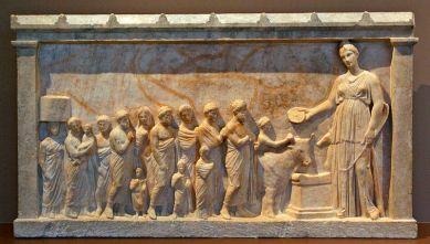 Αναθηματικό ανάγλυφο από το ναό τής Άρτεμης στη Βραυρώνα, περ. 350 π.Χ., Βραυρώνα, Αρχαιολογικό Μουσείο. Η Άρτεμη με τη Λητώ και τον Απόλλωνα δέχονται τους πιστούς με τις προσφορές τους.