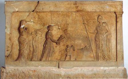 Αναθηματικό ανάγλυφο, τέλος 4ου-αρχές 3ου αιώνα π.Χ., Αρχαιολογικό Μουσείο Λαμίας. Σκηνή προσφοράς νεαρής μητέρας προς την Αρτέμιδα (Ειλειθυία-Λοχεία). Η γυναίκα εκφράζει τις ευχαριστίες της για τον καλό τοκετό του παιδιού της και για τη συνεχή προστασία του από τη θεά, η οποία εδώ εμφανίζεται με την ιδιότητά της ως Κουροτρόφου. Στην παράσταση εικονίζονται, από αριστερά προς τα δεξιά, μία πρεσβύτερη γυναικεία μορφή, που κρατάει πυξίδα στο αριστερό χέρι, μία θεραπαινίδα που στηρίζει στο κεφάλι της δίσκο με προσφορές (μήλο, ρόδι, γλυκά από μέλι, σταφύλι), η μητέρα με το βρέφος, ένας νεαρός δούλος, ο οποίος οδηγεί έναν ταύρο για θυσία στο βωμό και, τέλος, η θεά Άρτεμις στραμμένη προς τα αριστερά με δαυλό στο δεξί χέρι. Μοναδική είναι η απεικόνιση στο ανώτερο μέρος της παράστασης, με χαμηλό ανάγλυφο, των υποδημάτων και ενδυμάτων, τα οποία φορούσε η γυναίκα κατά τον τοκετό ή τα προμηθεύθηκε ειδικά για να τα αφιερώσει στη θεά. (πηγή: http://odysseus.culture.gr/h/4/gh430.jsp?obj_id=4662)