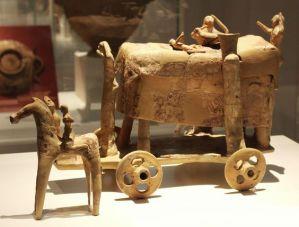 Πήλινο ομοίωμα άμαξας που μεταφέρει την νεκρική κλίνη, στολισμένη με κεντημένα υφασμάτινα στρωσίδια. Ο νεκρός κείται σκεπασμένος με το νεκρικό σεντόνι, ενώ τέσσερεις γυναίκες θρηνούν ολόγυρά του. Δίπλα στον νεκρό, ένα μισοξαπλωμένο παιδάκι υψώνει τα χέρια σε χειρονομία θρήνου. Από την Βάρη (αρχαίος Αναργυρούς), 7ος αι. π.Χ. Αθήνα, Εθνικό Αρχαιολογικό Μουσείο.