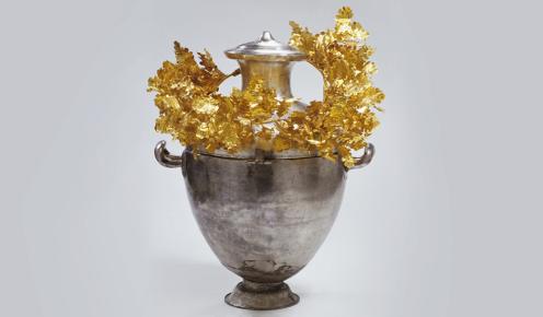 """Αργυρή οστεοδόχος υδρία, στεφανωμένη με το χρυσό στεφάνι δρυός. Μακεδονικός τάφος του """"Πρίγκηπα""""."""