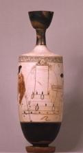 """Λευκή λήκυθος του """"ζωγράφου του Bosanquet"""", 440 π.Χ. Στο μέσο της σύνθεσης δεσπόζει μεγάλη επιτύμβια στήλη, με ανθεμωτή επίστεψη και ψηλή βαθμιδωτή βάση. Στα σκαλοπάτια του μνημείου έχουν εναποτεθεί διάφορες προσφορές για το νεκρό, κυρίως αγγεία και στεφάνια. Στη δεξιά πλευρά της στήλης, μία νέα γυναίκα φέρνει κάνιστρο με στεφάνια. Απέναντί της, αριστερά από τη στήλη, στέκεται νέος άνδρας, που φορεί μόνο ένα ιμάτιο και κρατεί δόρυ, προφανώς ο πρόωρα χαμένος σύντροφός της, Αθήνα, Εθνικό Αρχαιολογικό Μουσείο."""