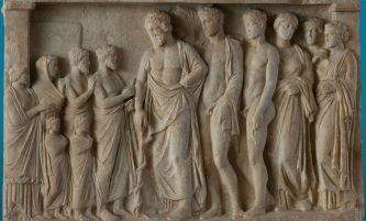 5β. Αναθηματικό ανάγλυφο από τη βίλα του Ηρώδη Αττικού στη Λουκού Κυνουρίας, ο Ασκληπιός με τους γιους του Ποδαλείριο και Μαχάονα και τρεις κόρες του (δεξιά), δέχεται μια οικογένεια πιστών, 4ος π.Χ. αιώνας, Εθνικό Αρχαιολογικό Μουσείο.