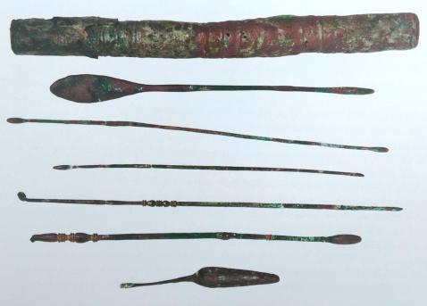 """39α. Κυλινδρική θήκη με πώμα. Περιείχε ιατρικά εργαλεία από κράμα χαλκού - κασσίτερου/χαλκού-ψευδάργυρου (σπαθομήλη, διπύρηνο μήλη, μήλη, μηλωτίδα ή ωτογλυφίδα και δύο κυαθισκομήλες). Από τον """"τάφο του χειρουργού"""", Ανατολική Νεκρόπολη της Νέας Πάφου, Επαρχιακό Μουσείο Πάφου"""